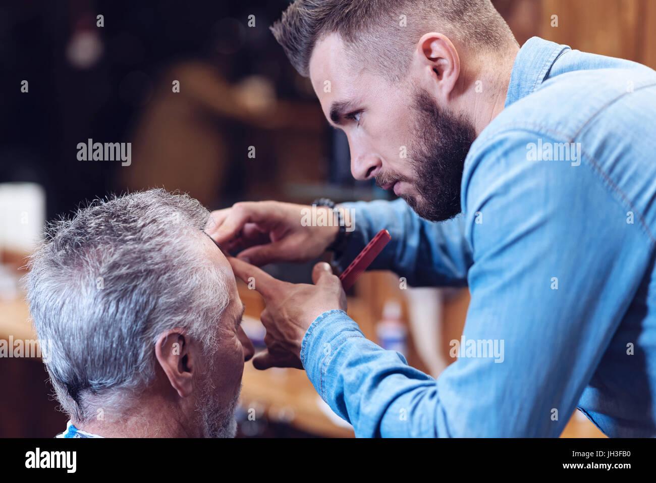 Nice handsome barber doing a haircut - Stock Image