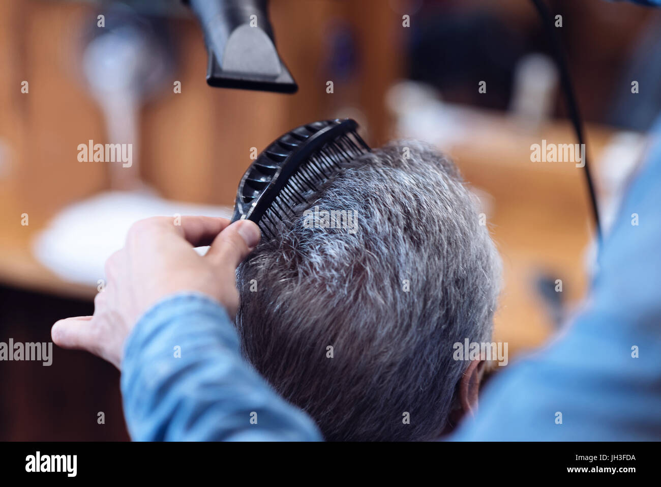 Professional nice barber styling his clients hair - Stock Image