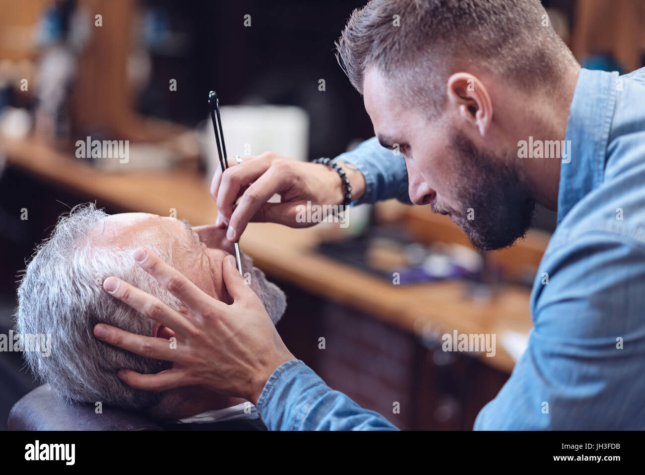 Nice serious barber shaving his client - Stock Image