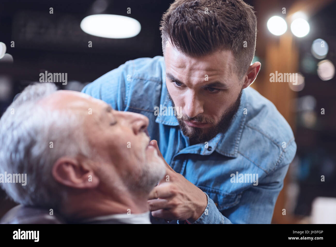 Serious handsome hairdresser looking at his client - Stock Image