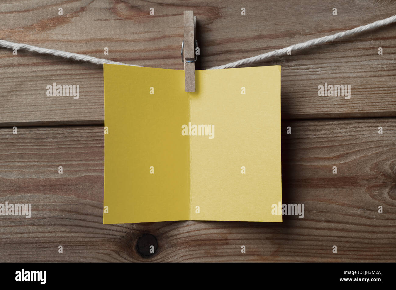 An opened, blank yellow greetings card,  pegged on to string against wood plank background - Stock Image