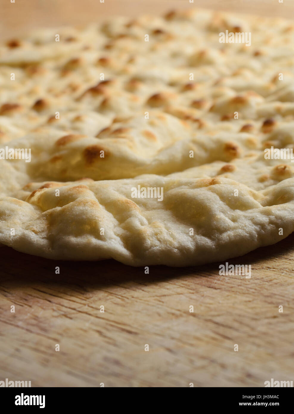 A bare, shop-bought  pizza base, ready to be topped, on an old wooden chopping board. Stock Photo