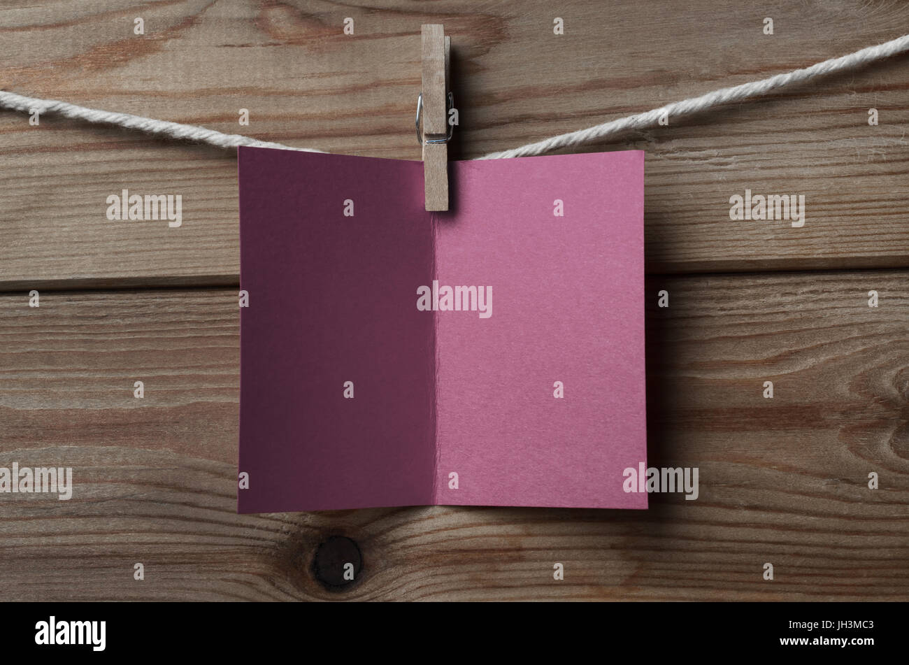 An opened, blank plum greeting or Christmas card, pegged on to string against wood plank background - Stock Image