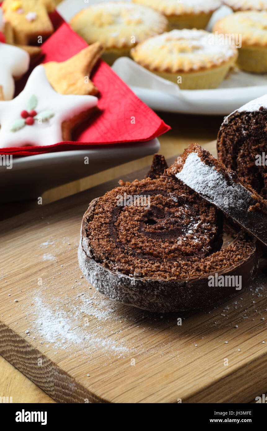 Chocolate Christmas Yule Log on wooden board with decorated biscuits and mince pies in background. - Stock Image