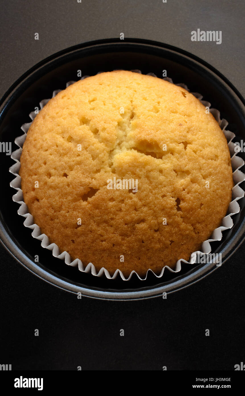 Overhead close up of a single cup cake in paper case, in recess of black bun tin. Stock Photo