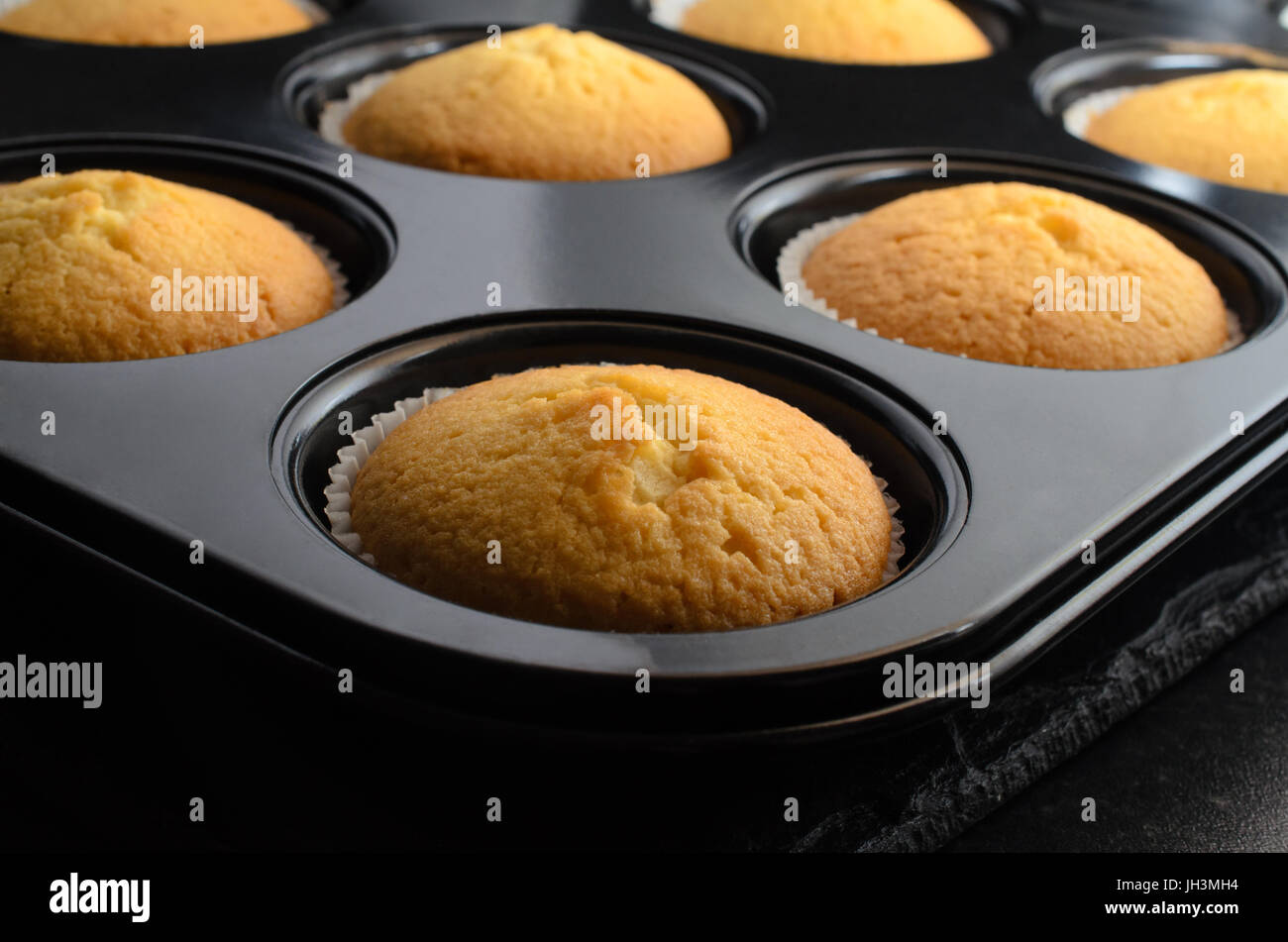 Home baking concept with multiple vanilla cupcakes, in paper cases inside bun tin, cooling on black slate. Stock Photo