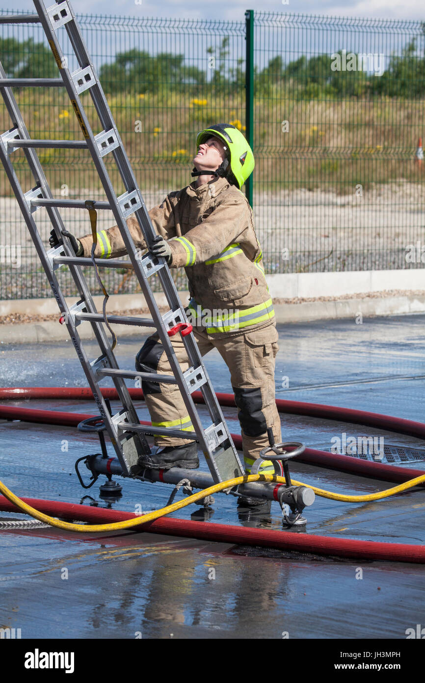 firefighter anchoring ladder at ground level - Stock Image