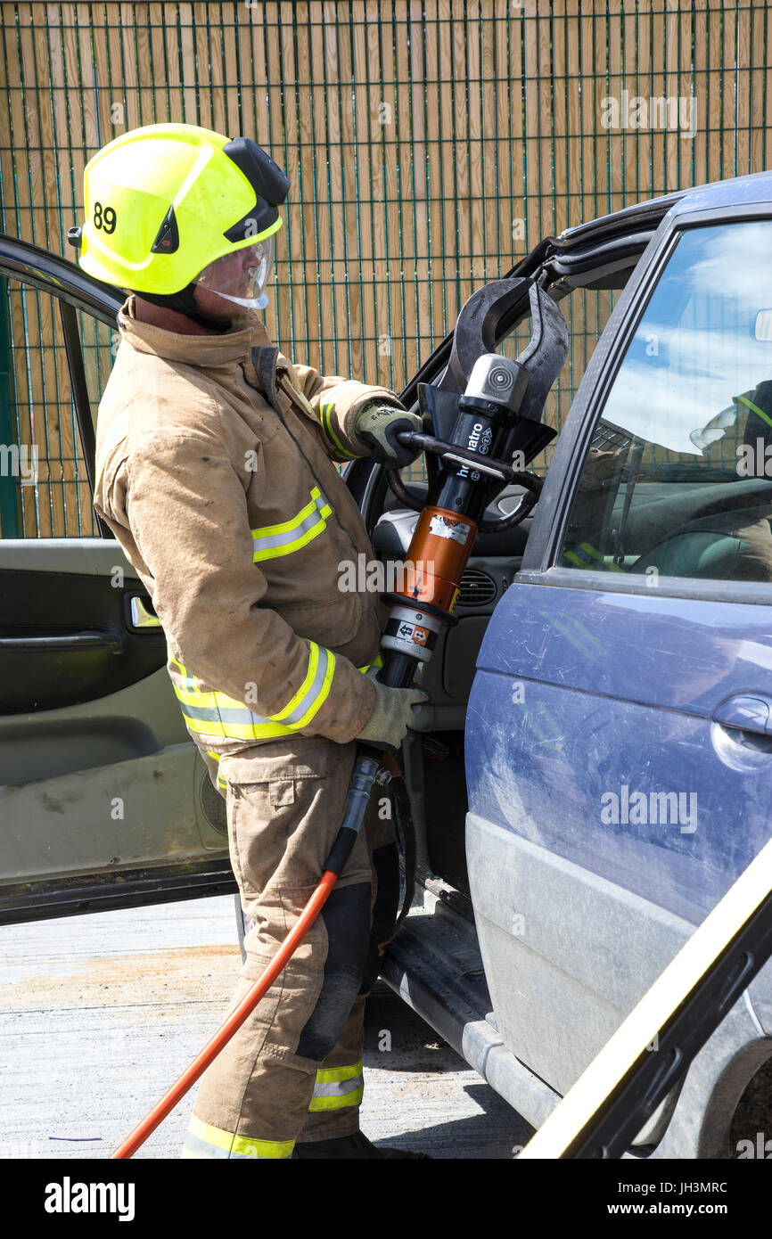 Firefighter training to cut open car - Stock Image