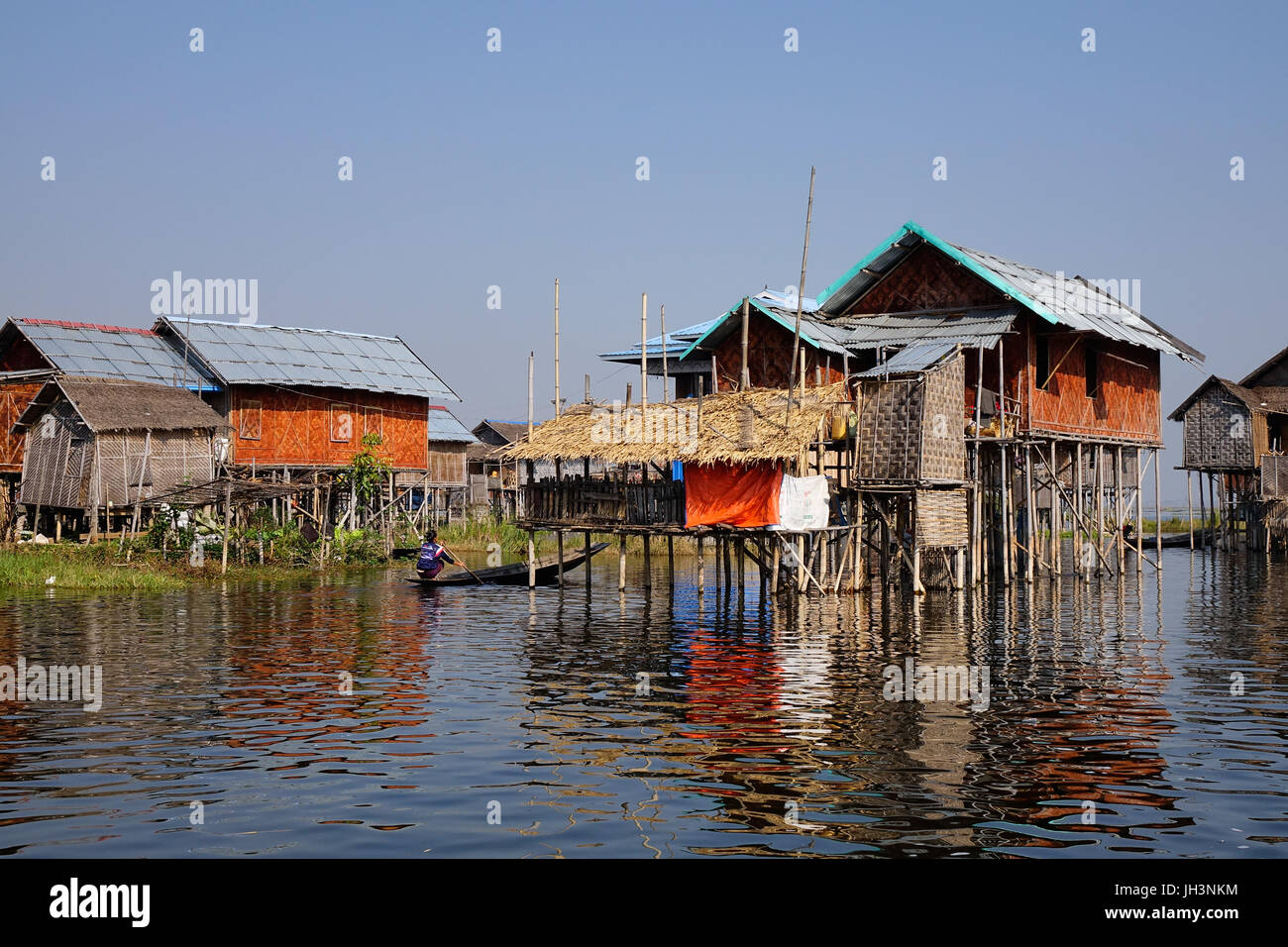 Burmese woman rowing boat at the village on Inle lake, Shan state, Myanmar. Inle Lake is a major tourist attraction, - Stock Image