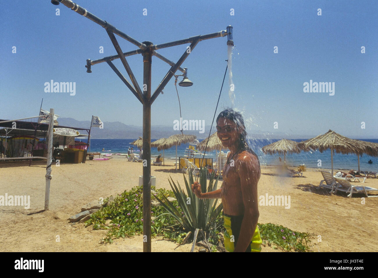 A young man cooling off under a beach shower. Eilat, Israel - Stock Image