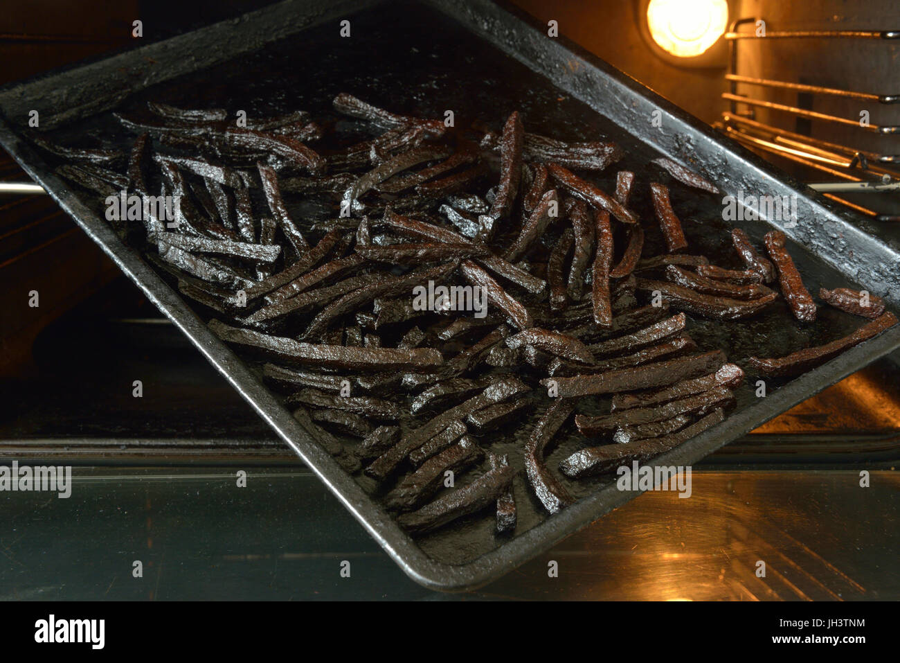 Burnt oven cooked french fries - Stock Image