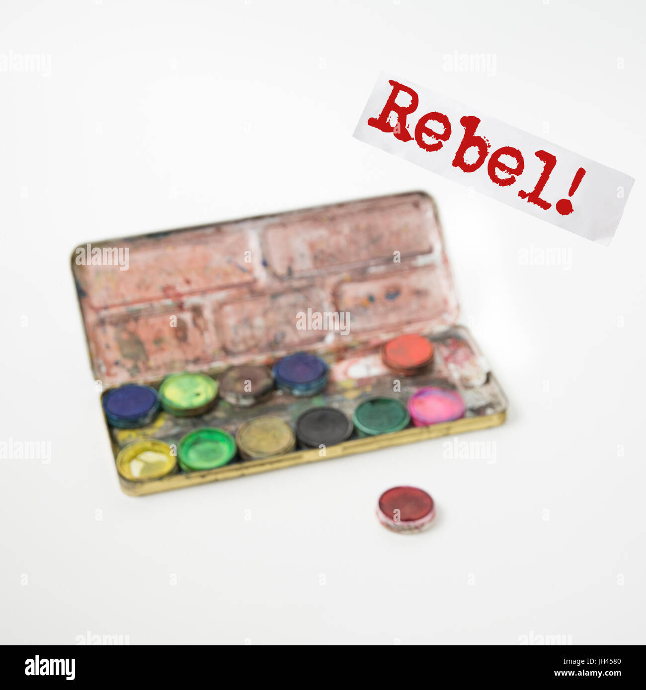 Rebel! Outlaw. Renegade. A concept made out of gouache set. Text in focus. Gouache set blurry. - Stock Image