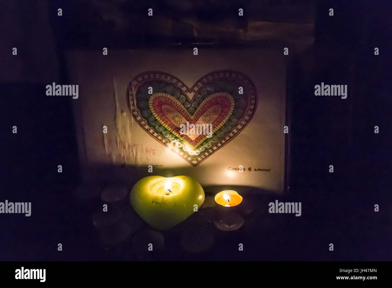 heart shaped candle glimmering a colored heart drawing. Spontaneous homage at the victims of the terrorist attacks - Stock Image