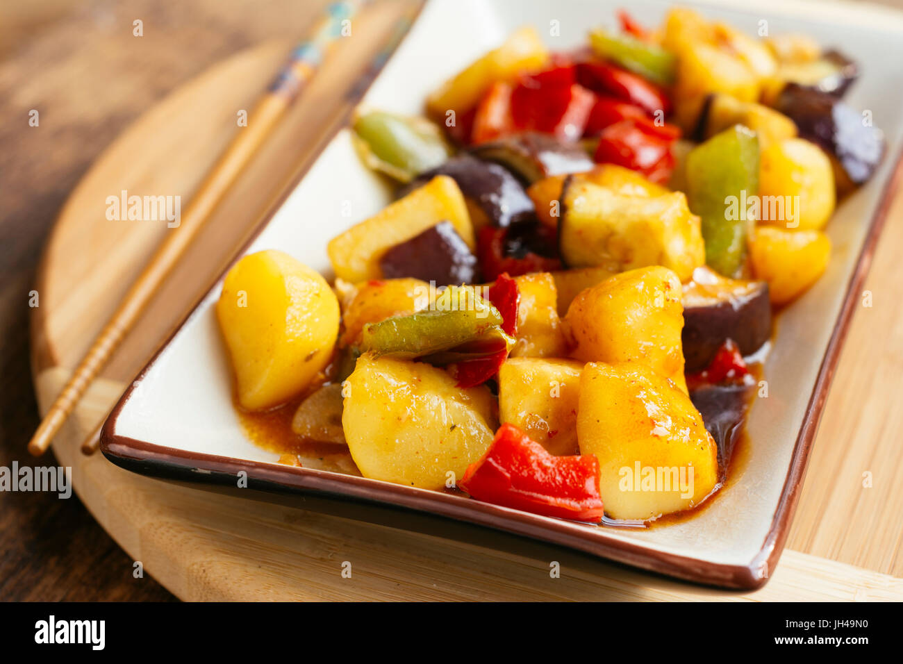 Stir-fried potatoes with eggplant and bell pepper. Stock Photo