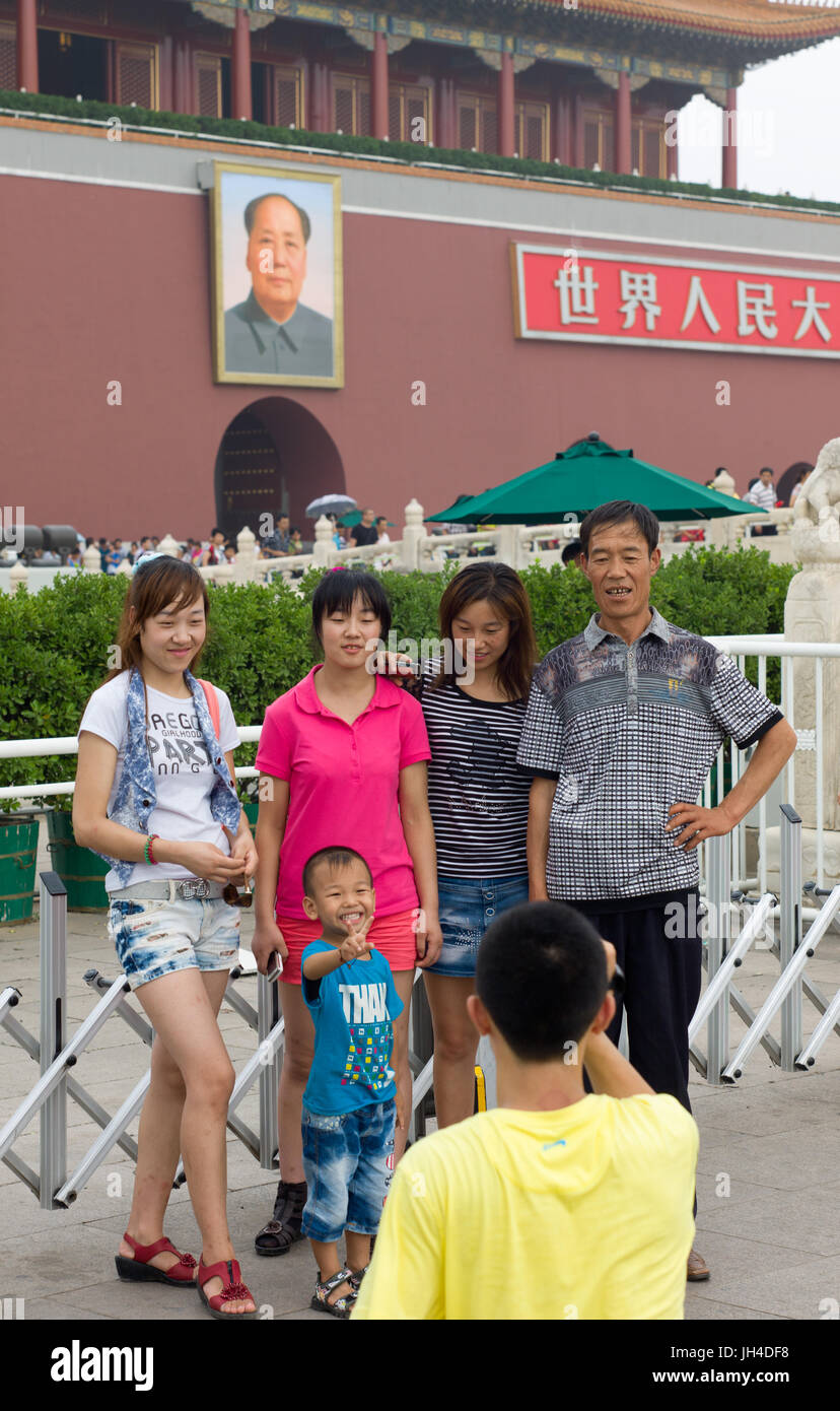 Family poses for photograph outside Forbidden City, with portrait of Mao Zedong in background. Beijing, China - Stock Image