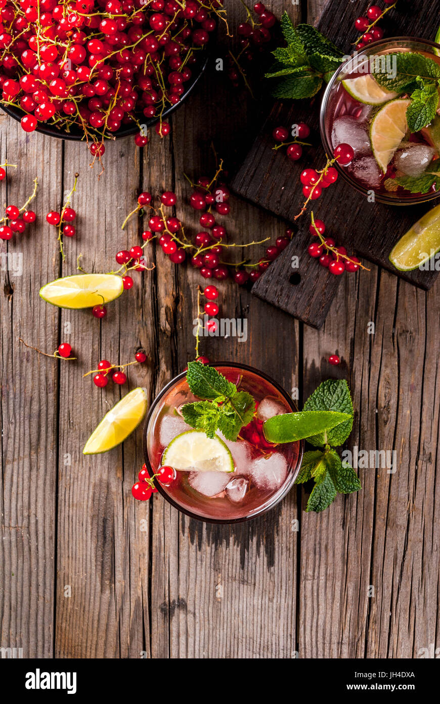 Ideas of summer drinks, dietary healthy cocktails. Mojito from lime, mint and red currant. On the old rustic wooden - Stock Image