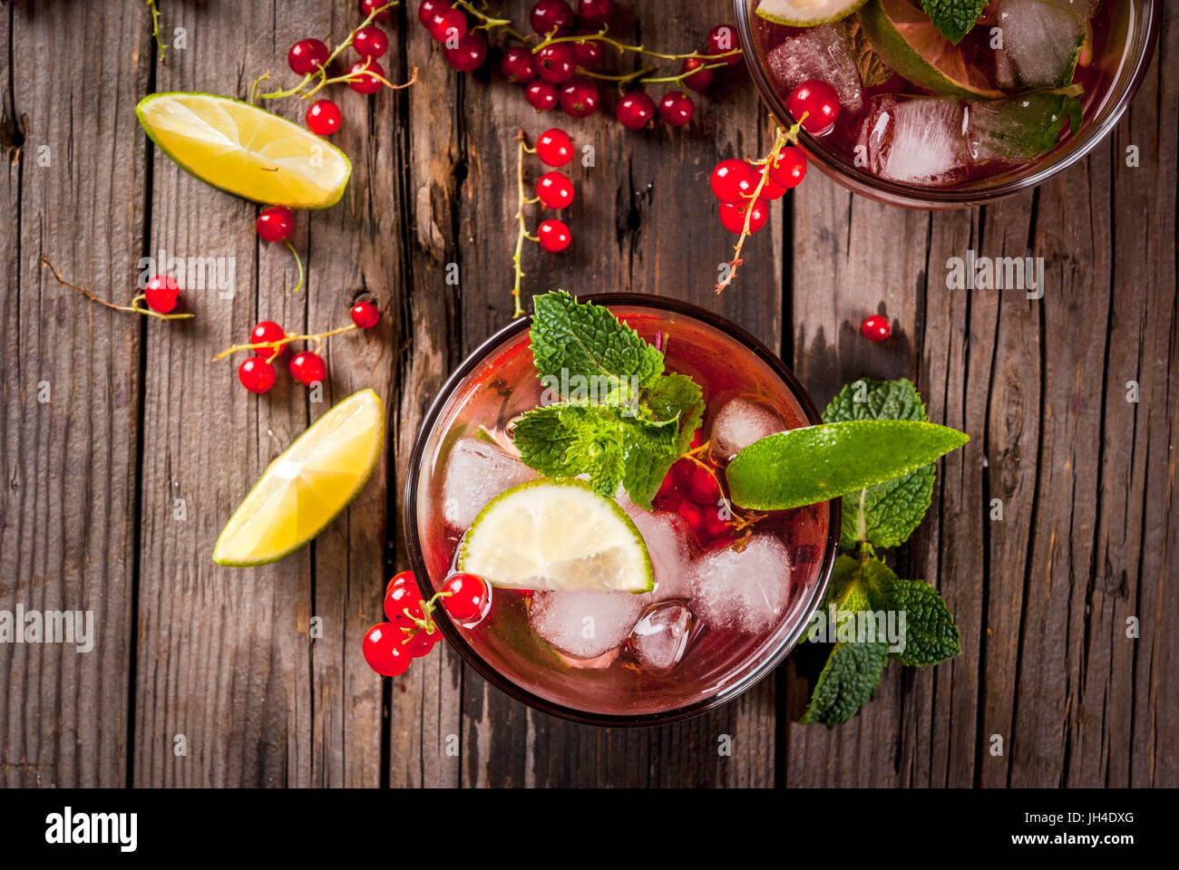 Ideas of summer drinks, dietary healthy cocktails. Mojito from lime, mint and red currant. On the old rustic wooden Stock Photo