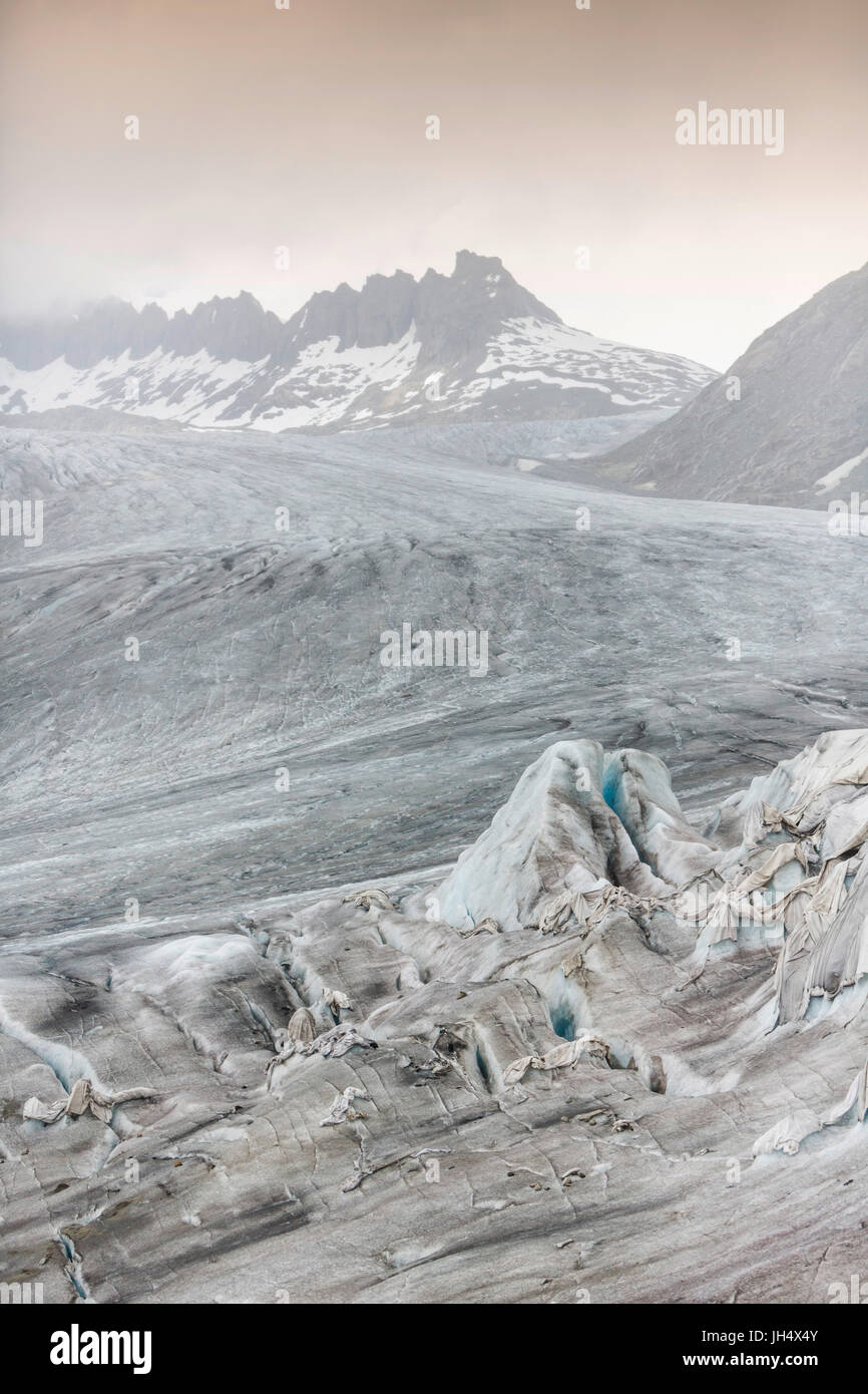 Glacier melt close up: The Rhone glacier is partially squeezed with cloths to slow the melting proc Stock Photo
