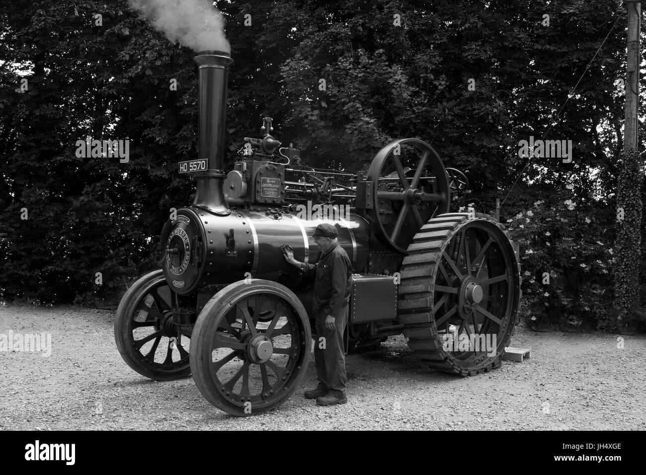 Black and White shot of a steam traction engine. Driver polishing the boiler on a machine that is in full steam Stock Photo