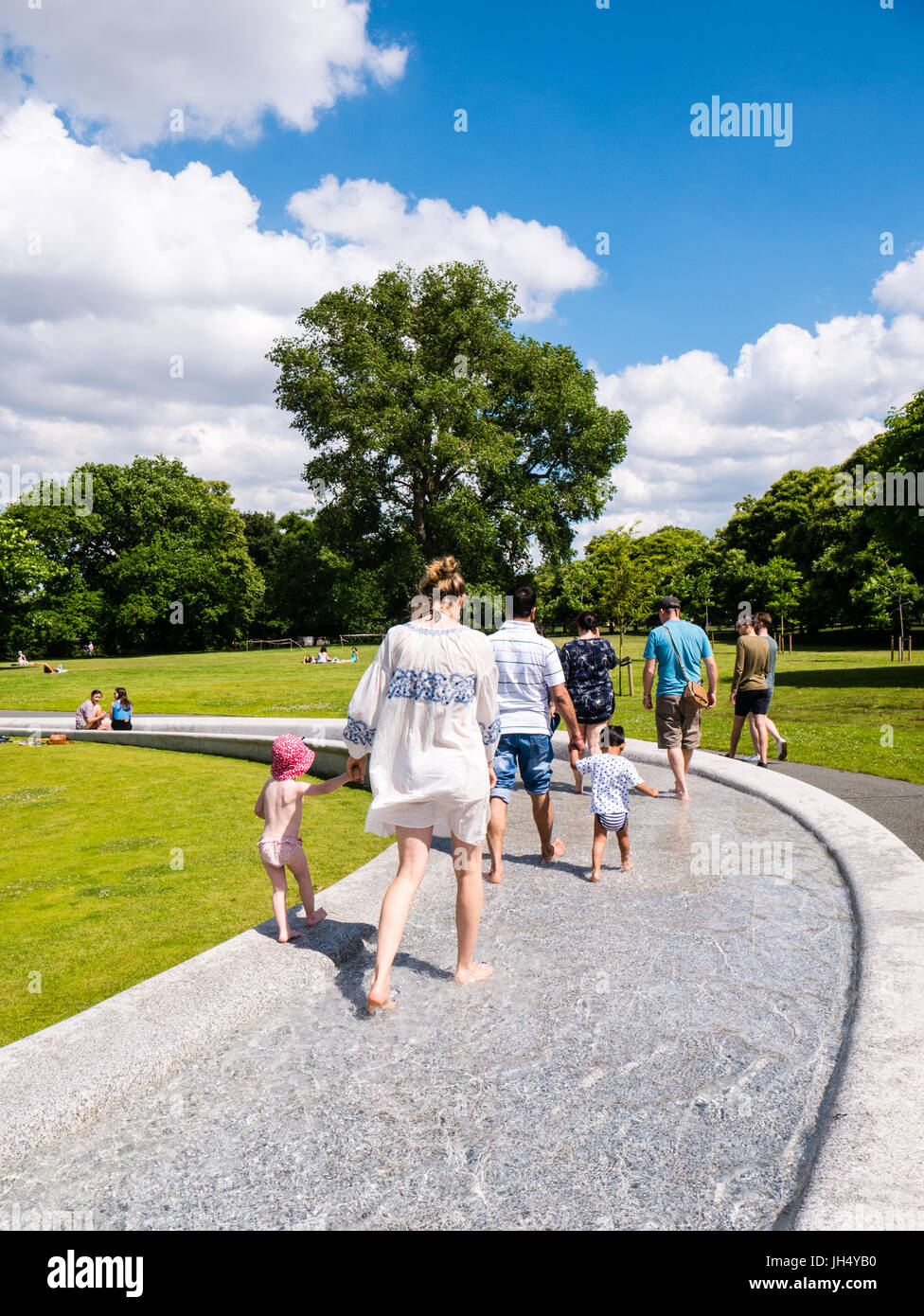 People Enjoying Sunshine, Princess Diana Memorial Fountain, Hyde Park, London, England Stock Photo