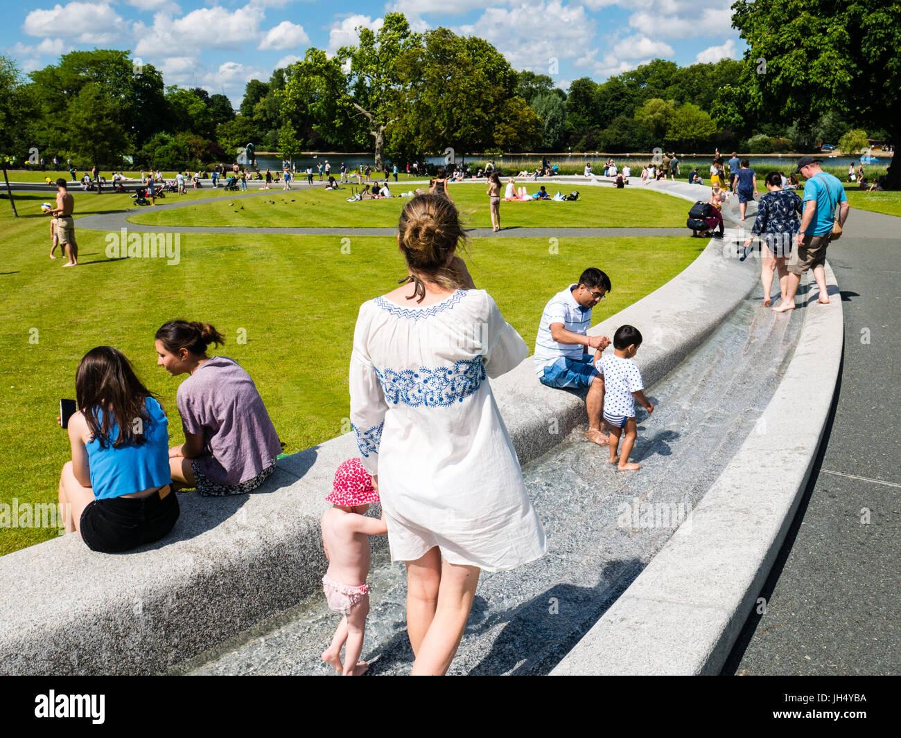 People Enjoying Sunshine, Princess Diana Memorial Fountain, Hyde Park, London, England - Stock Image