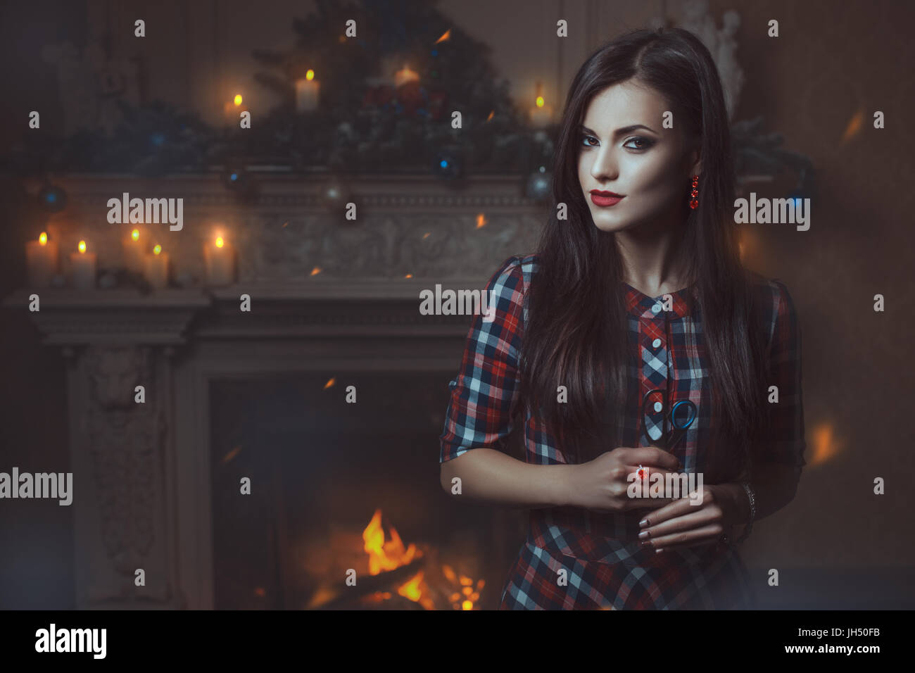 Girl witch with a pair of scissors in his hand standing in front of the fireplace and looks. - Stock Image