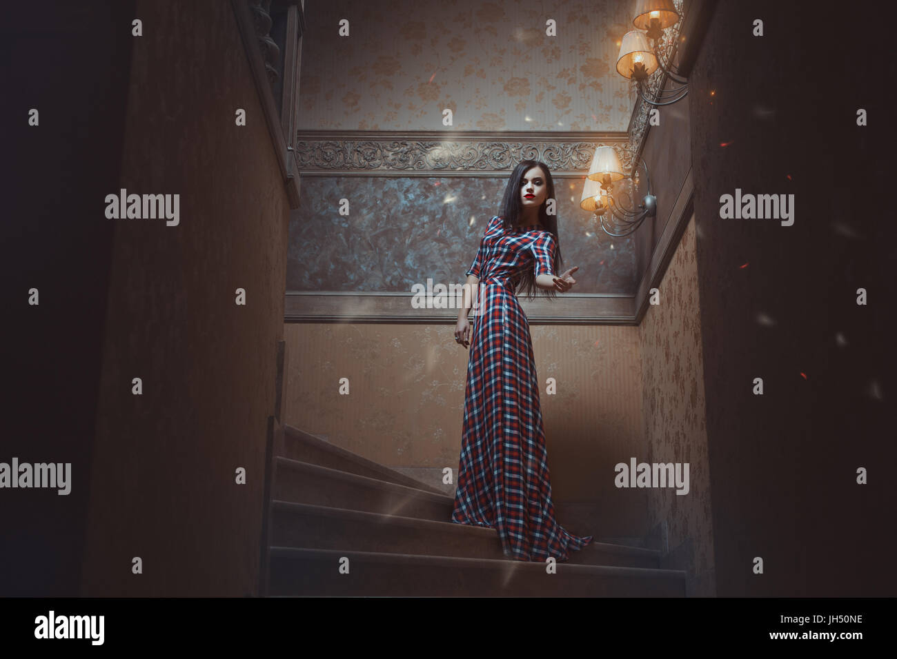 Mystical girl standing on the stairs and conjures. - Stock Image