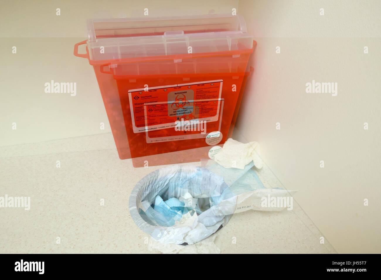 A red bio hazard box with a trash can hole spilling out garbage. - Stock Image