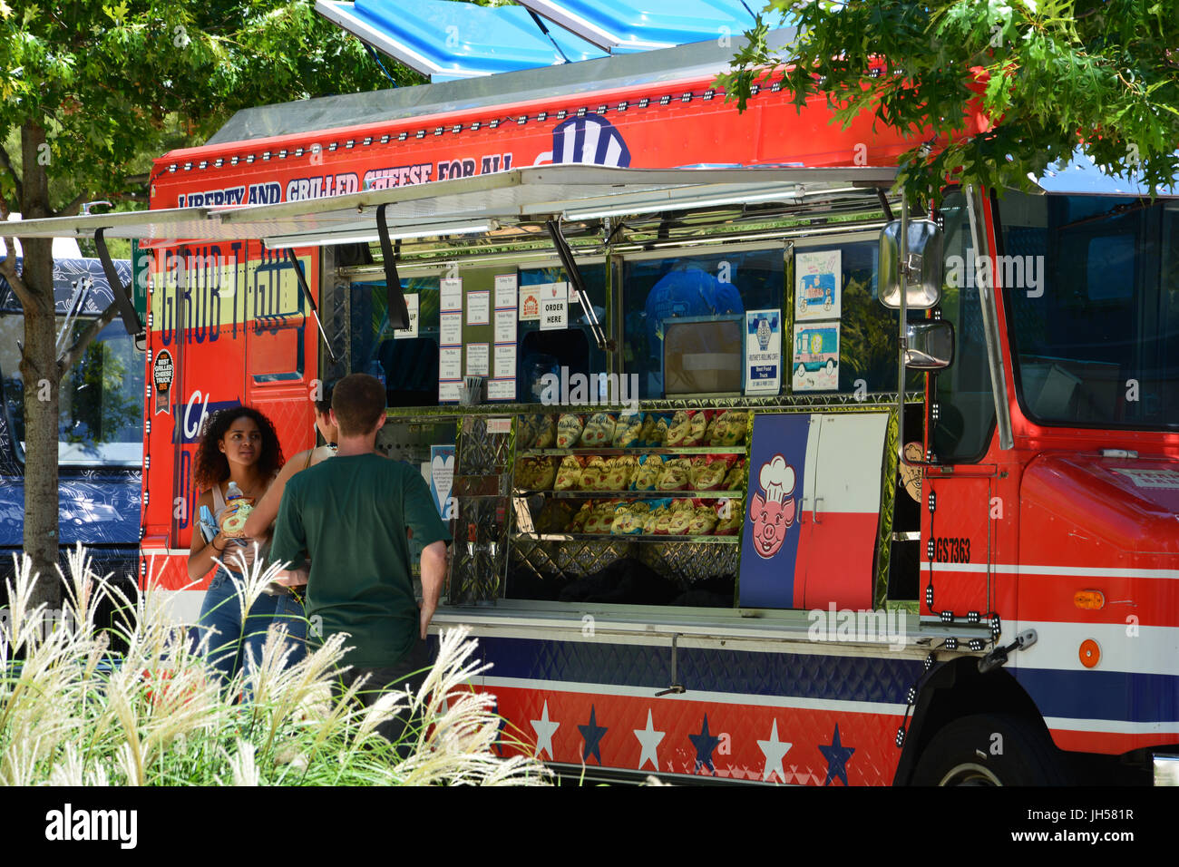 Food trucks line up during the day next to Klyde Warren Park in downtown Dallas Stock Photo