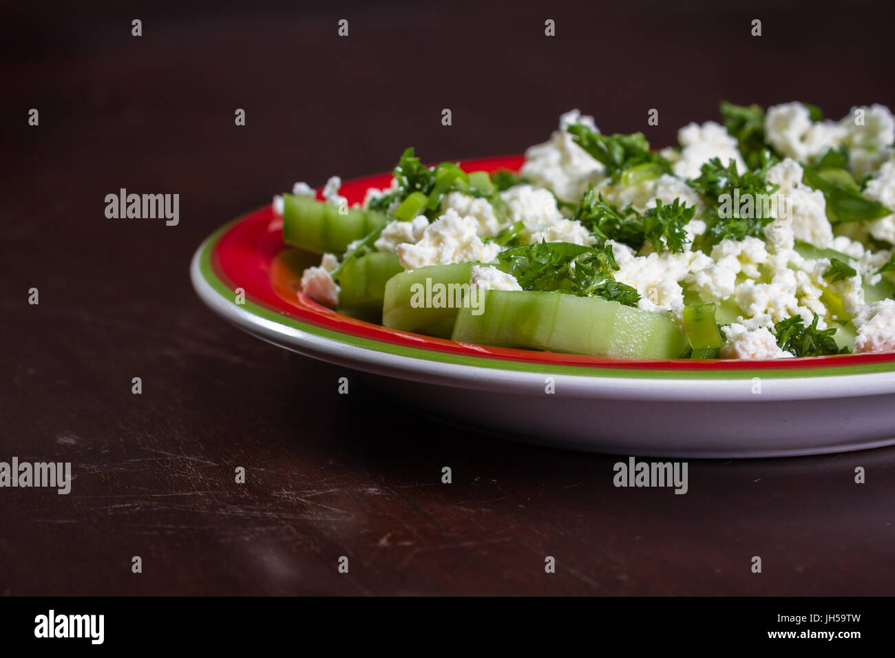 close up of a cucumber and feta cheese salad topped with green onion and parsley dressed with olive oil and lemon - Stock Image