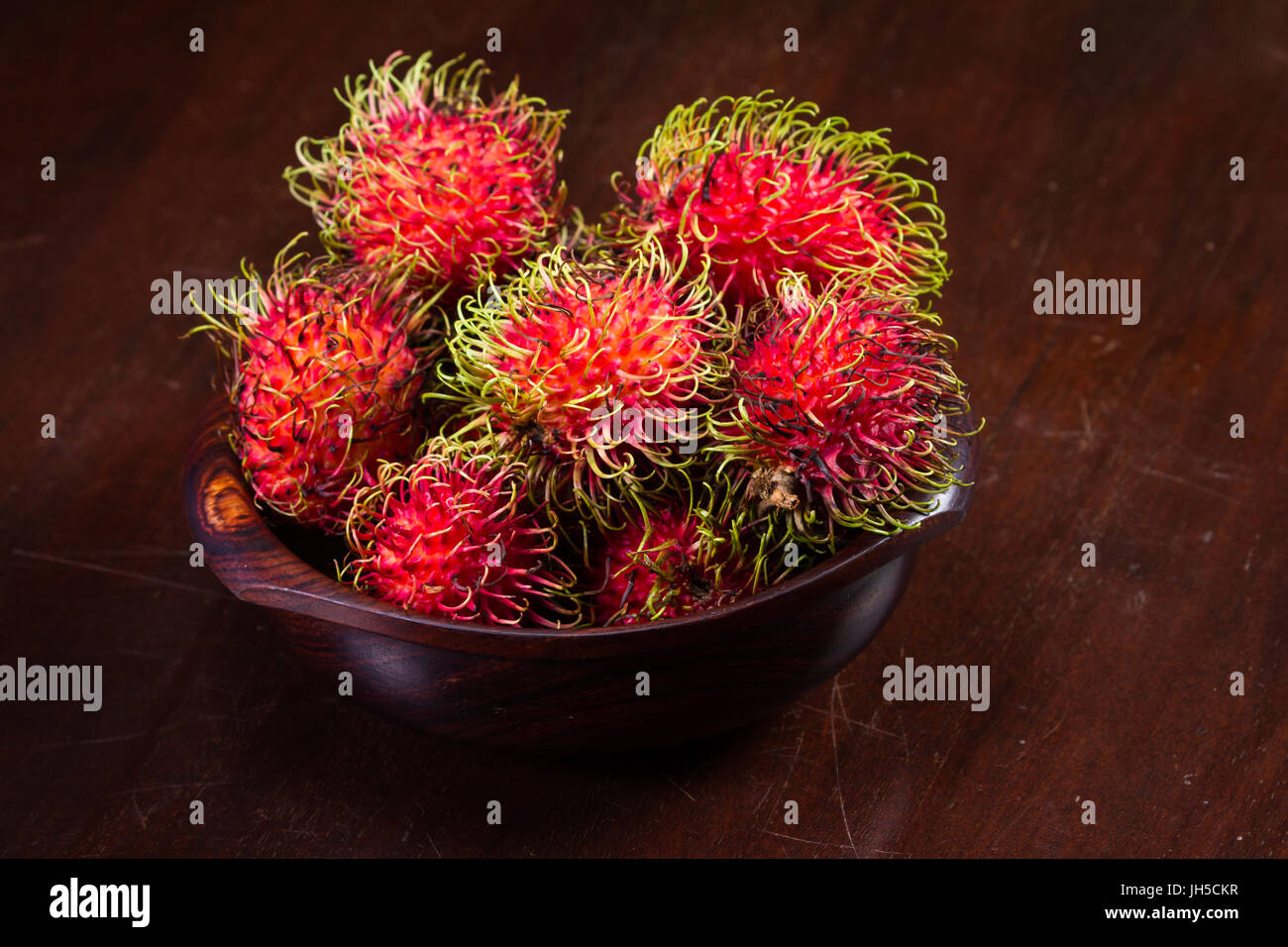 wooden bowl filled with rambutan placed on a wooden table, Rambutan is a sweet tropical fruit. - Stock Image