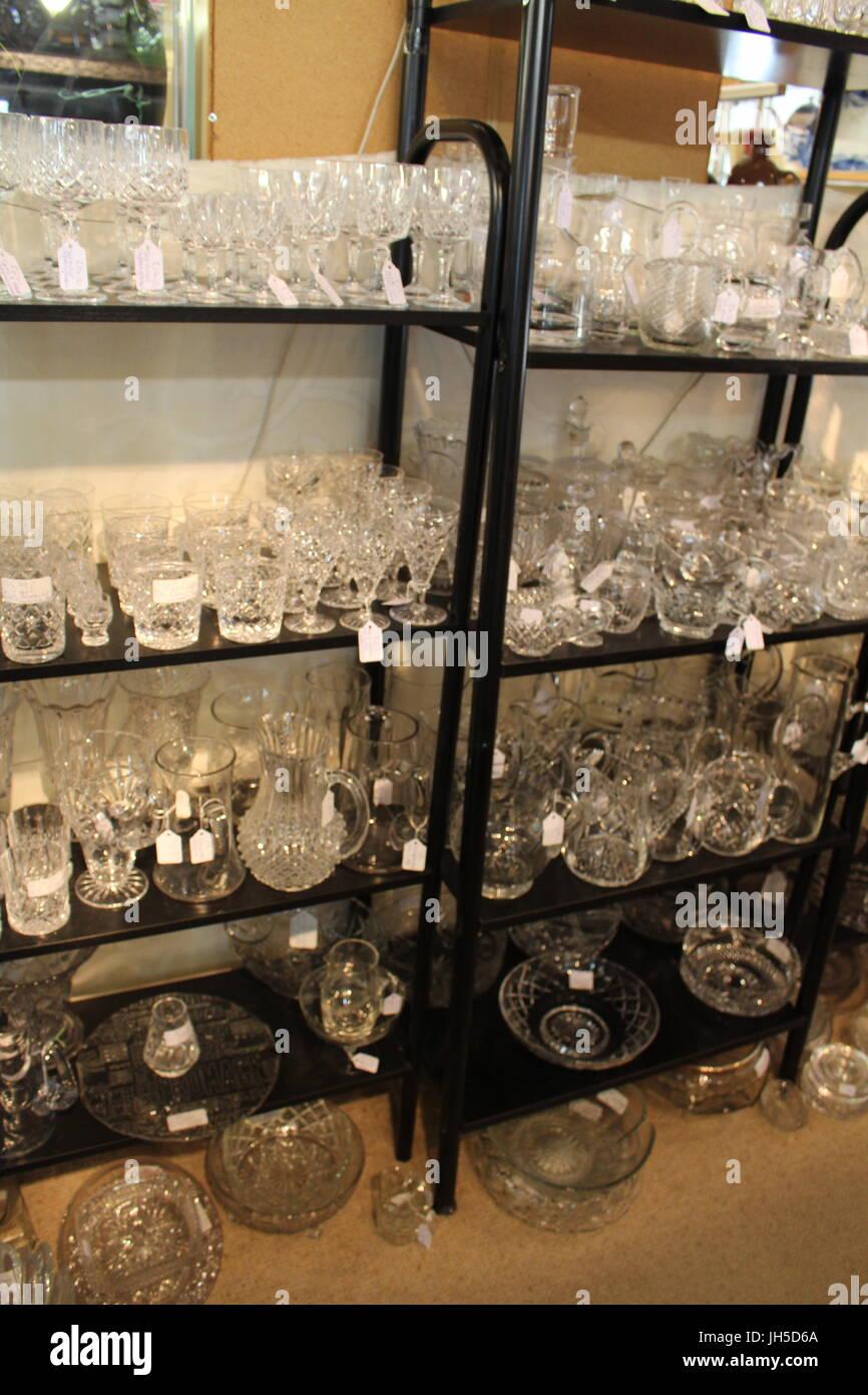 clear glass, glass ornaments, glasses, glass vases, fragile, glass on shelf, glasses on shelf, charity shop, antique - Stock Image