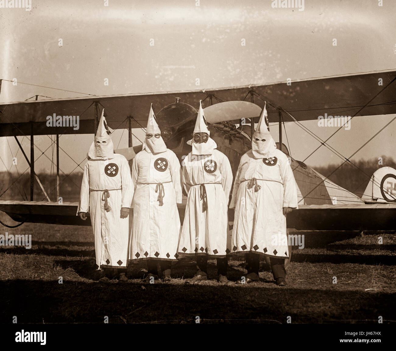 Ku Klux Klansmen use a biplane to drop and distribute KKK leaflets over the American countryside. Stock Photo