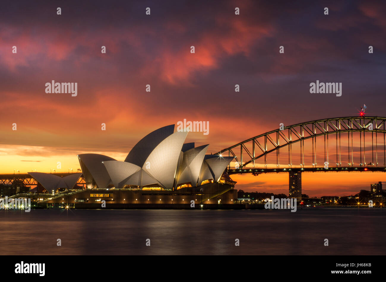 Sydney Opera House illuminated at sunset - Stock Image