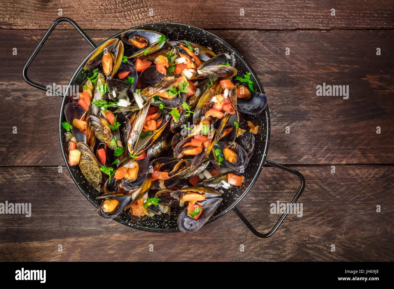 Skillet of marinara mussels on rustic background with copyspace Stock Photo