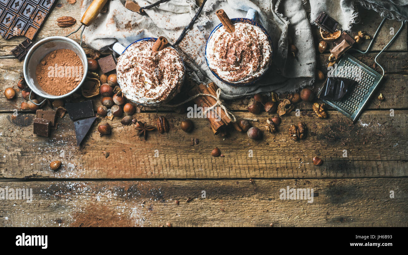 Hot chocolate with whipped cream and cinnamon sticks served with anise stars, different nuts and cocoa powder on - Stock Image