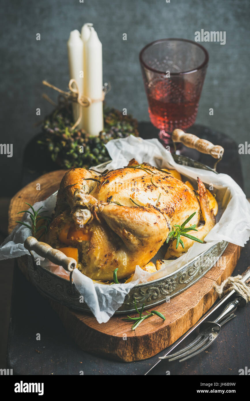 Christmas table set with oven roasted whole chicken and wine - Stock Image