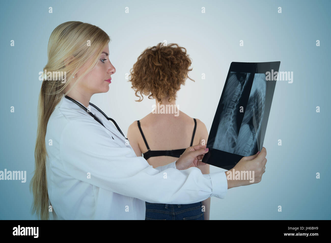 Young blonde female orthopedic doctor visits young patient with stethoscope - Stock Image