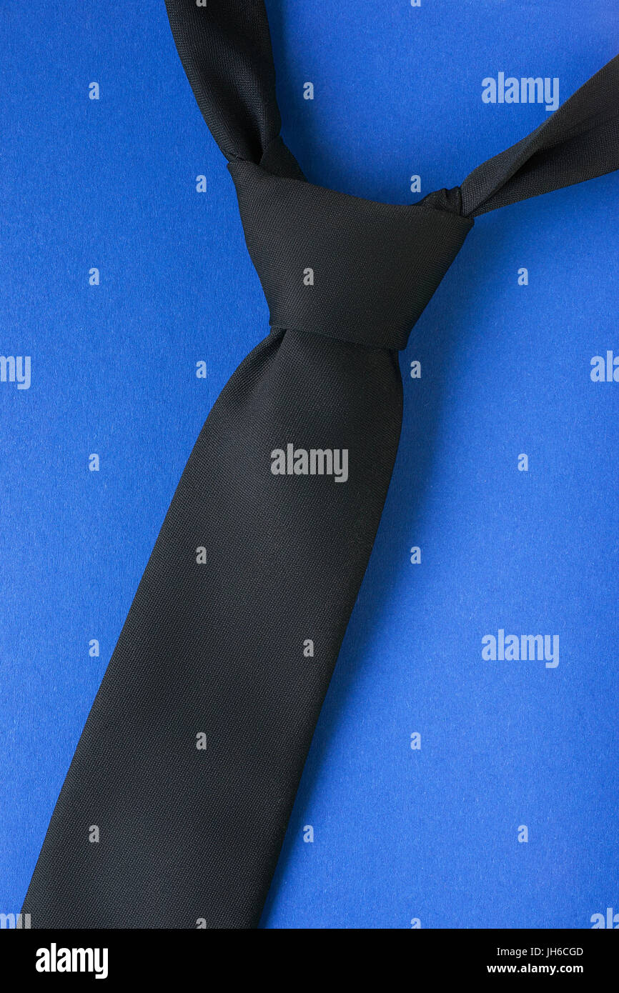black tie with windsor knot on blue background man style theme