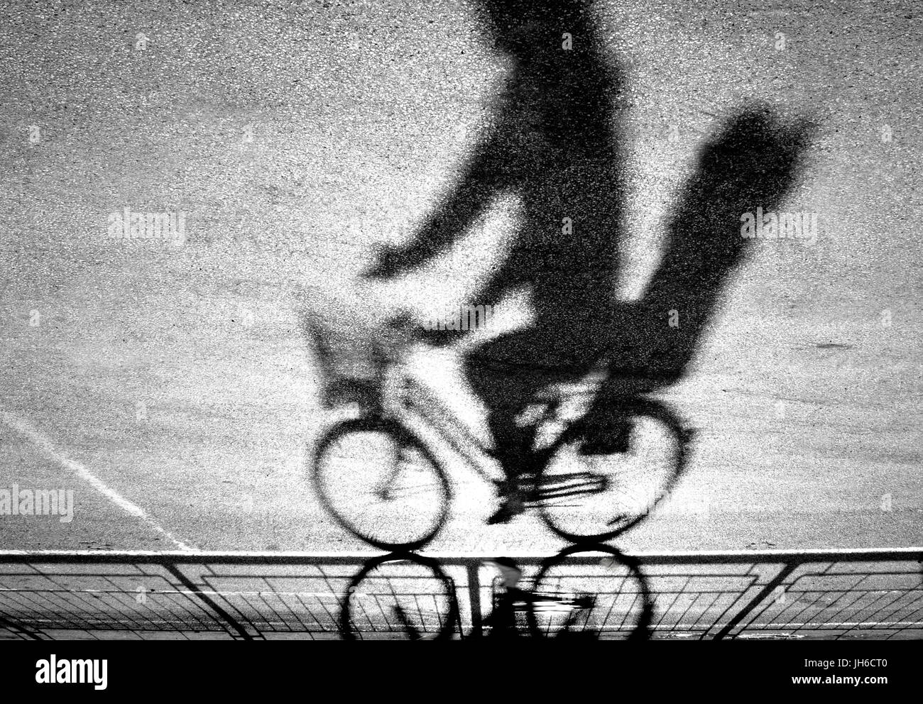Blurry cyclist with kid rear seat silhouette and shadow on a protected bike path in black and white upside down - Stock Image