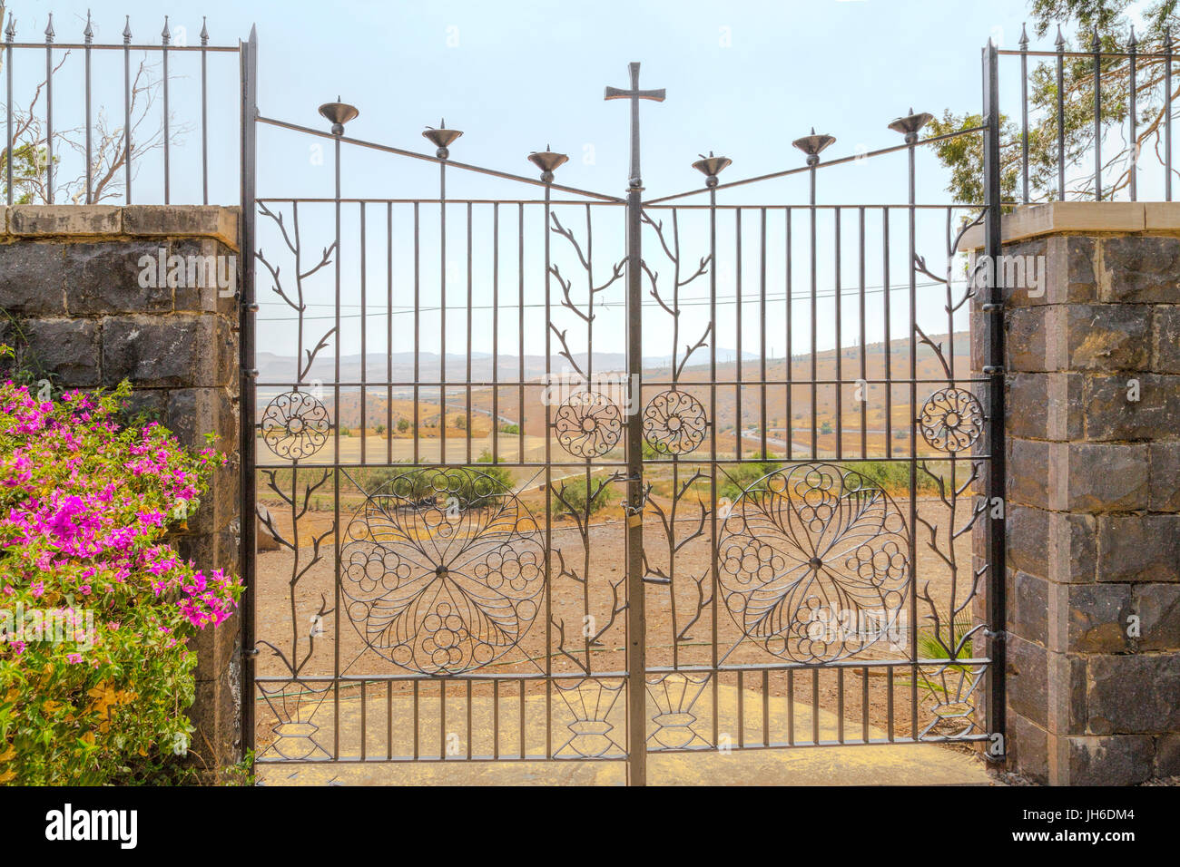 Wrought-iron fence with floral design and cross on top in the Cloister Garden of Beatitudes Church, overlooking Stock Photo