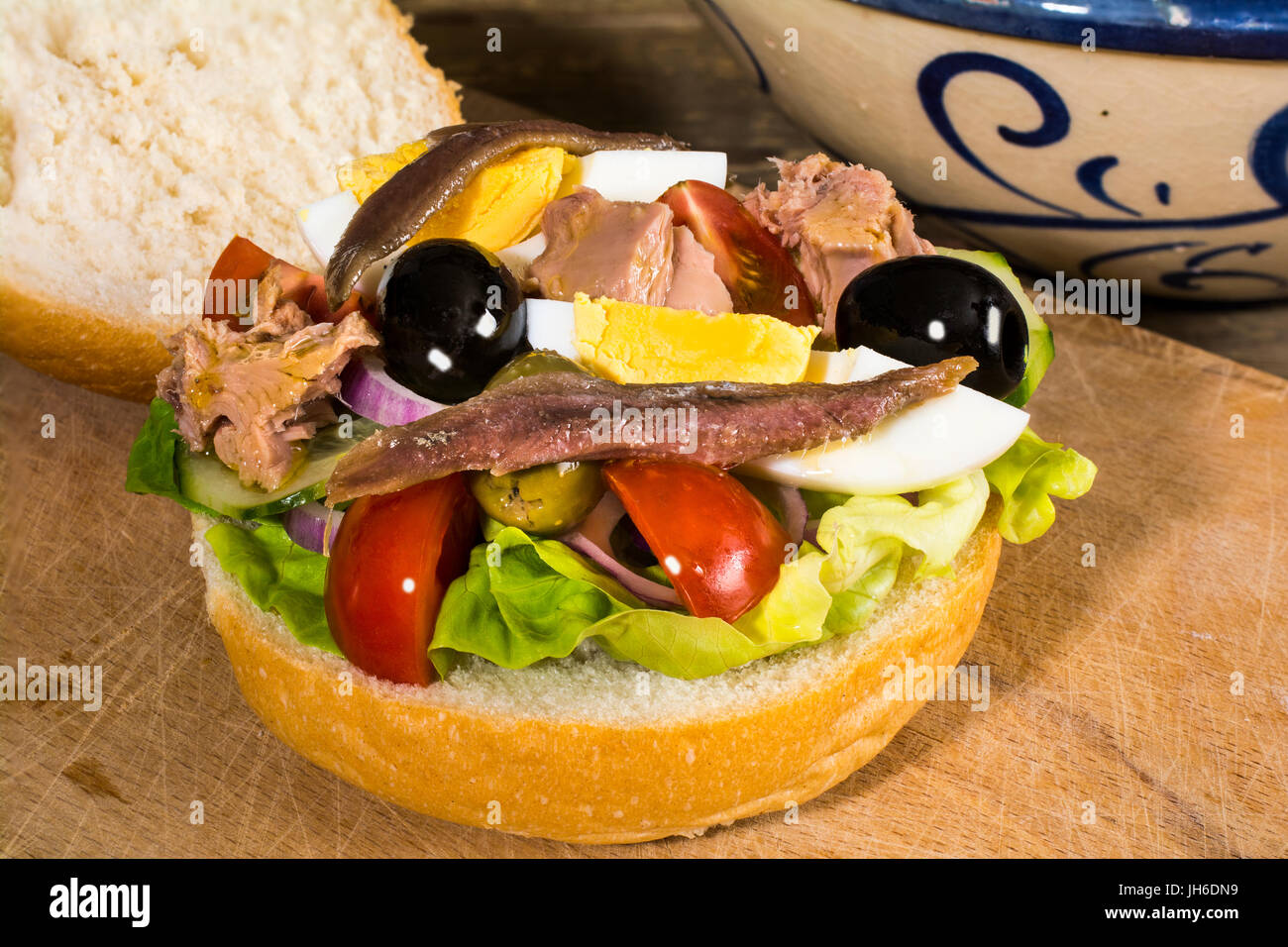 Genuine Pan Bagnat, traditional salad sandwich from Nice Cote d'Azur, France: lettuce, tomato,onion, cucumber, - Stock Image