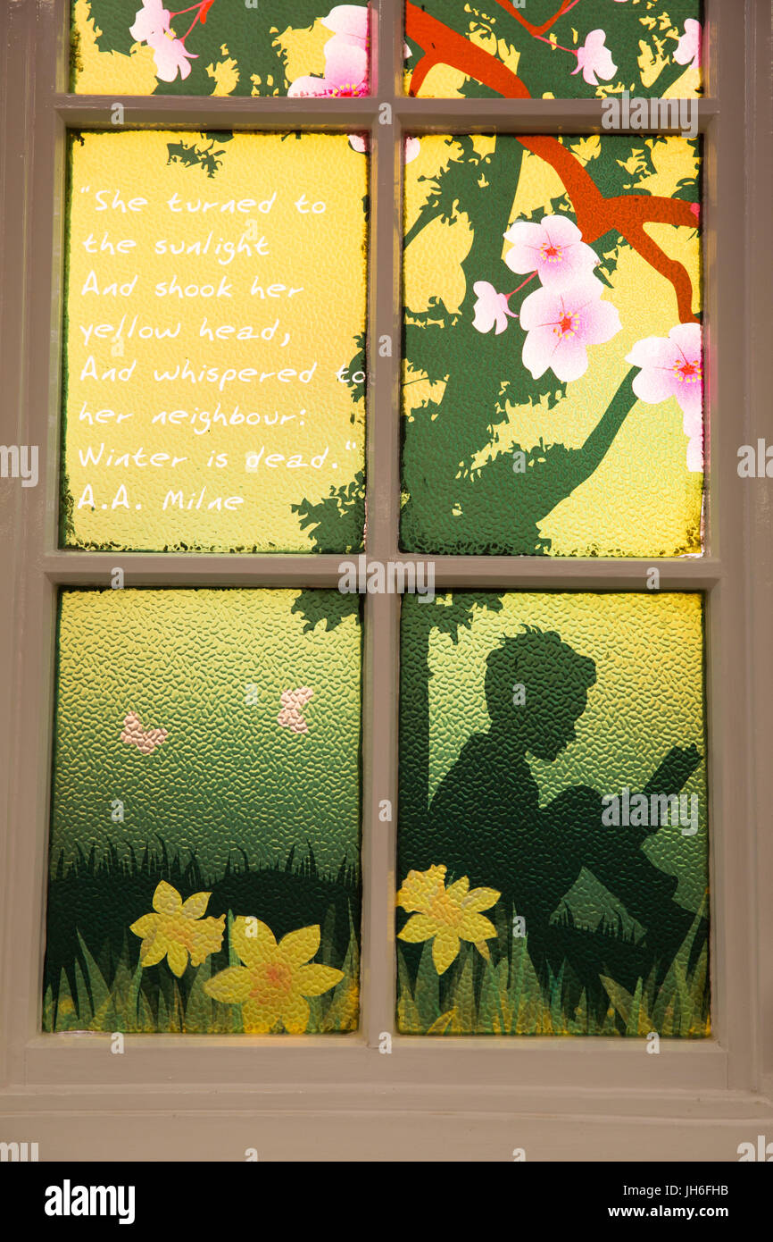 A window in Stratford upon Avon Library painted with the words of writer A A Milne - Stock Image