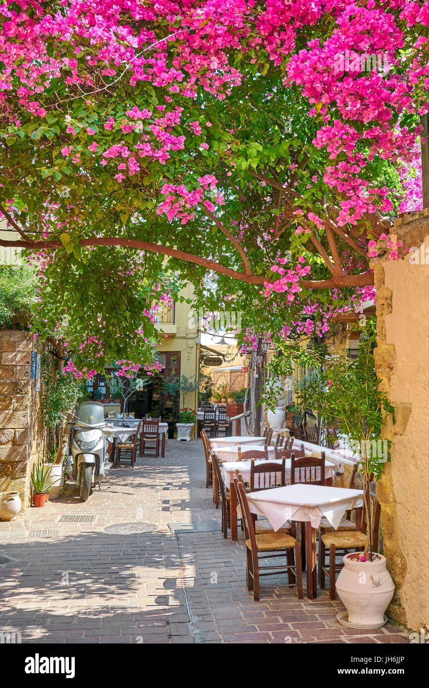 Restaurant at Chania Old Town, bougainvillea blooming flowers, Crete Island, Greece - Stock Image