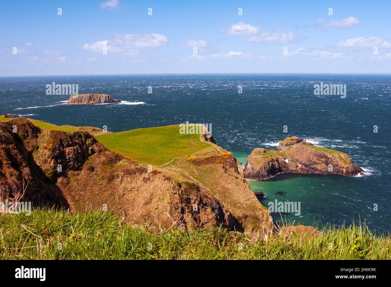 Carrick-a-Rede rope bridge and the Atlantic Ocean on a sunny and windy day, Ballintoy, Northern Ireland - Stock Image