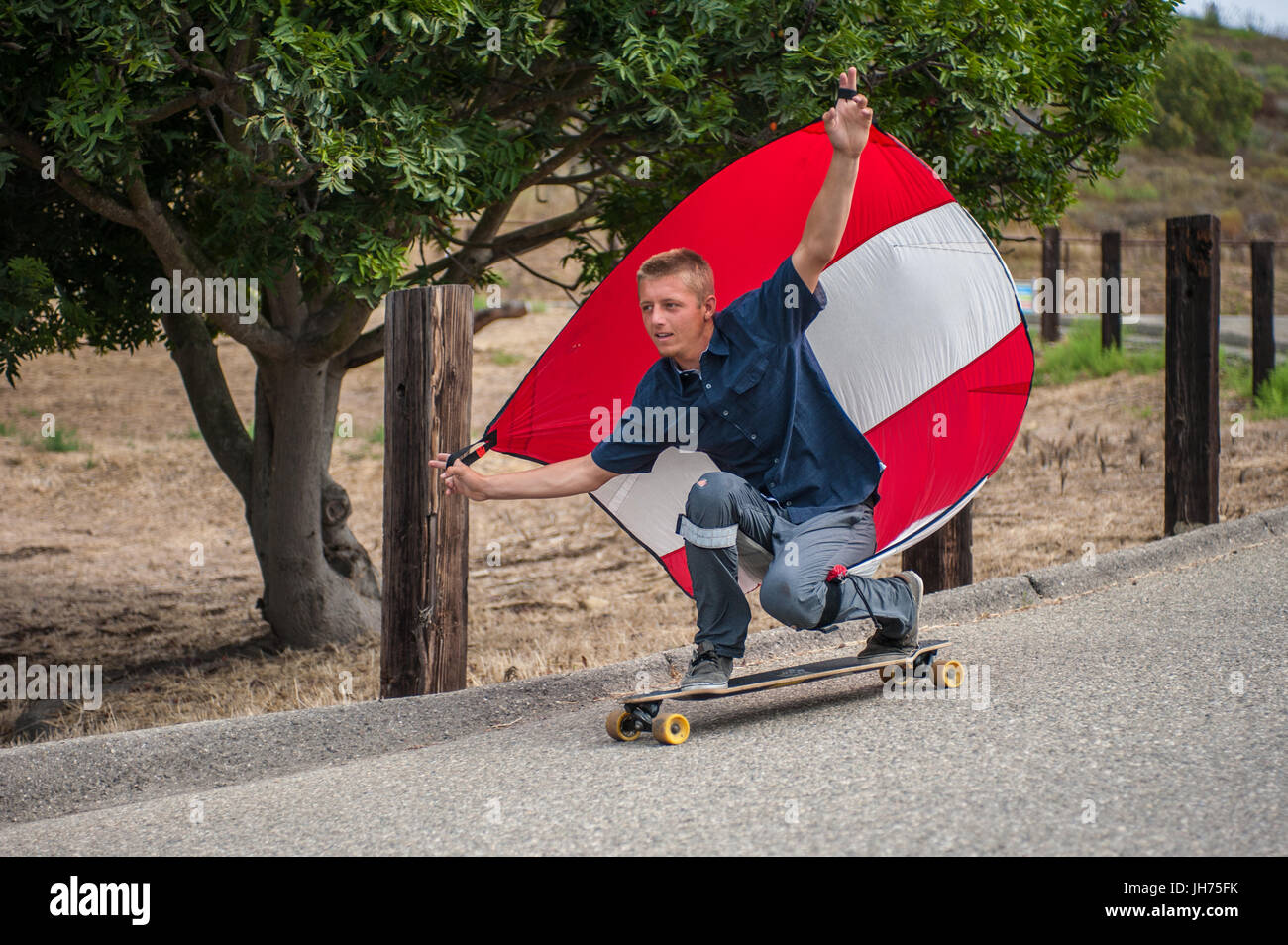Parachute downhill skateboarder has sail full of wind as he crouches in goofy foot stance. Stock Photo