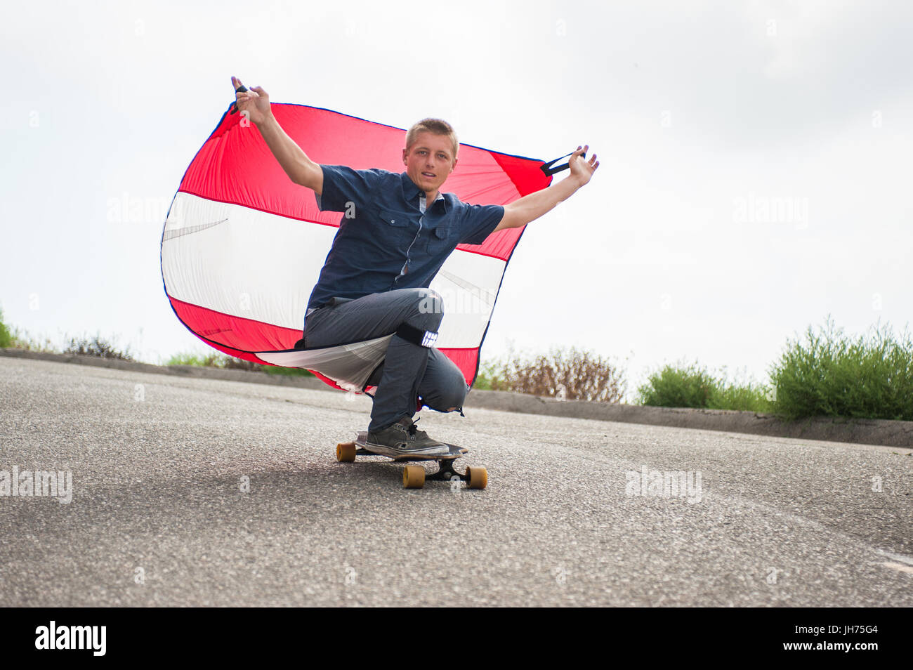 Parachute downhill skateboarder has sail full of wind as he crouches on board. Stock Photo