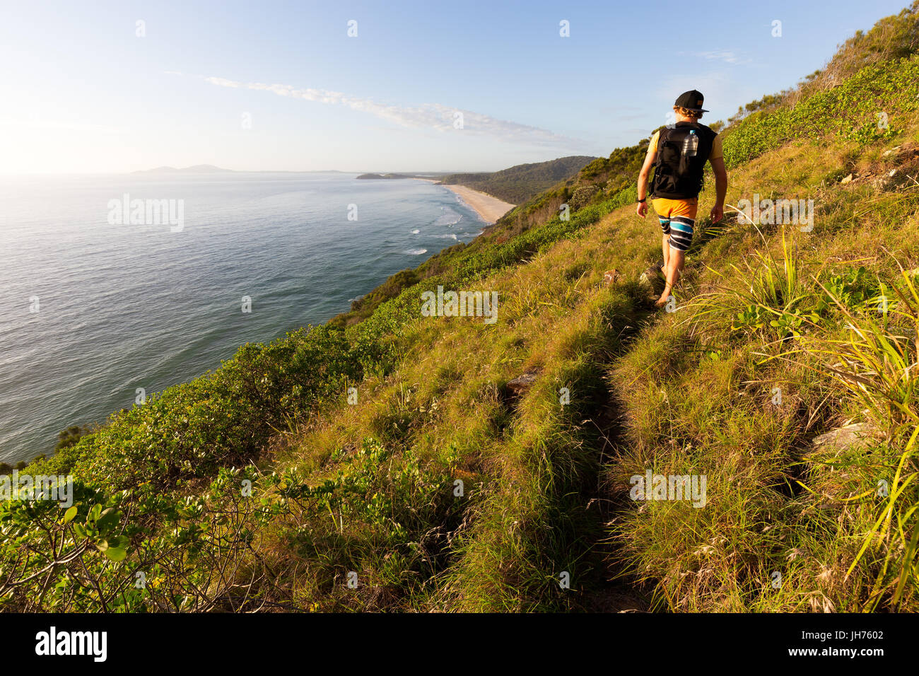 A hiker looking at a beautiful coastline view over the sea during a bright summer morning as he walks on a grassy - Stock Image
