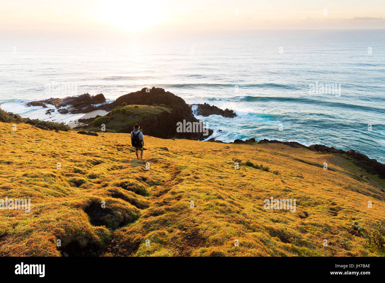 A person on a grassy headland watches the sunrise over the sea and a beautiful coastline in Australia. - Stock Image