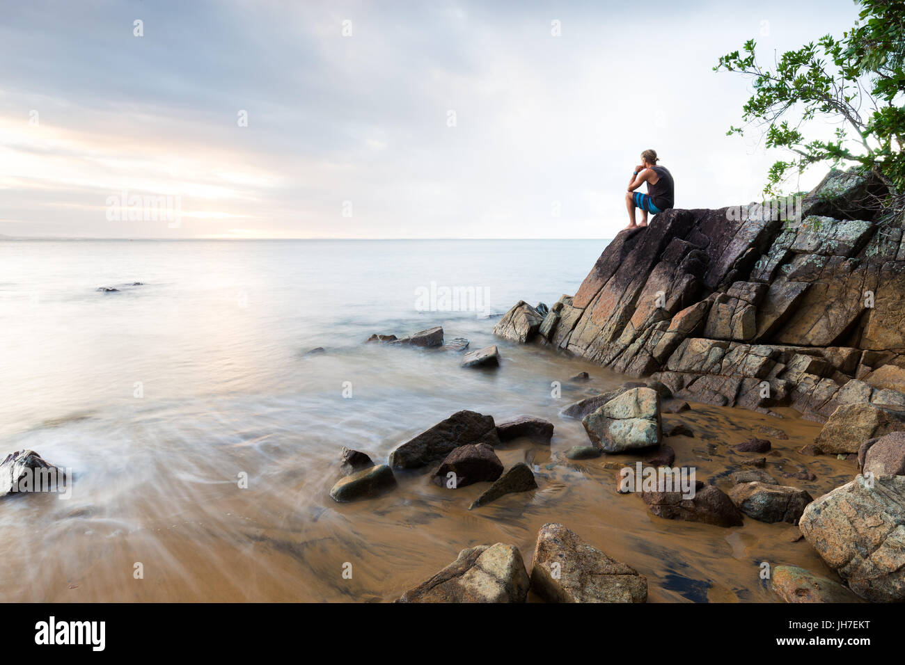 A man sits on a boulder in contemplation at a beautiful beach in a long exposure seascape scene. - Stock Image